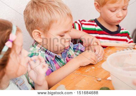 Cute children sculpt something from grey plasticine in kindergarten