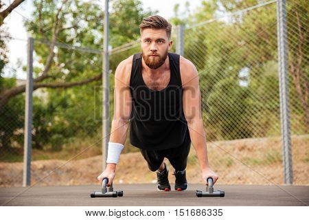 Handsome young fitness man doing push-up exercises with sport equipment outdoors