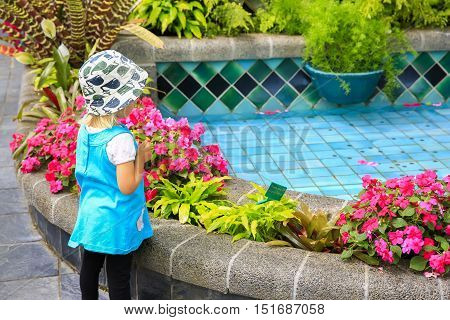 Little Girl In A Blue Dress Is Looking At Wishing Fountain In Begonia House , Wellington
