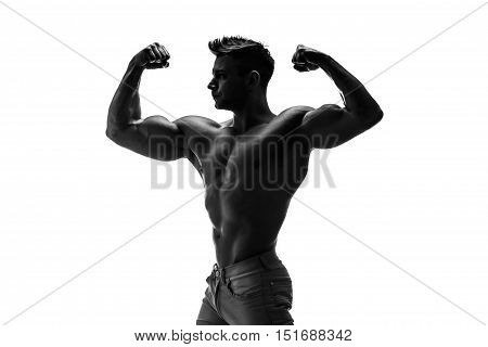 The beautiful and strong young guy.  Black and white photo, silhouette. Hidden in the shadow.  Male silhouette.