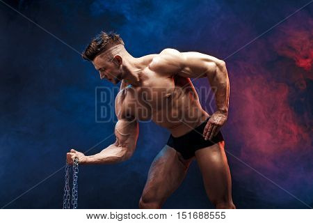 handsome power athletic man bodybuilder doing exercises with chain. Fitness muscular body on dark smoky background. Perfect male. Awesome bodybuilder, posing.