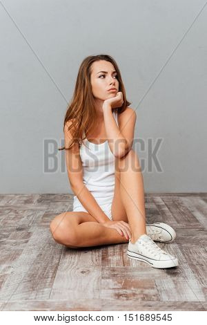 Pensive young casual woman sitting on the floor and looking away isolated on a gray background