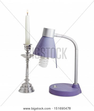Light fixture with compact fluorescent lamp and burning candle in an old metal candlestick on a light background