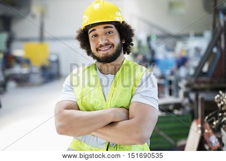 Portrait of smiling male manual worker standing arms crossed in industry