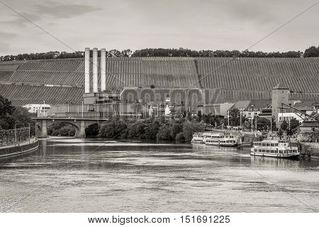 Wurzburg Germany - May 22 2016: Cogeneration plant and vineyards on the Main river bank in Wurzburg Franconia Bavaria Germany. Black and white photography sepia toned.