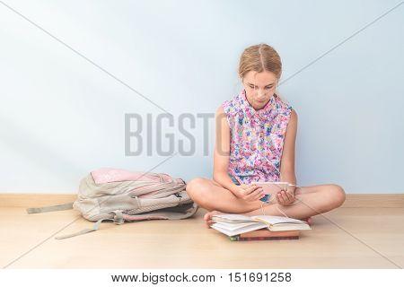 Schoolgirl reading a book in classroom at school
