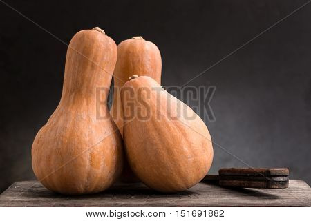 still life of pumpkins on a wooden board.