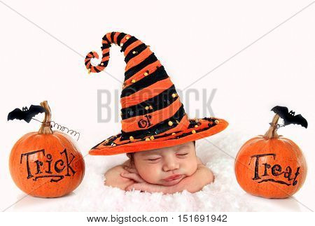 Halloween baby with trick or treat pumpkins.
