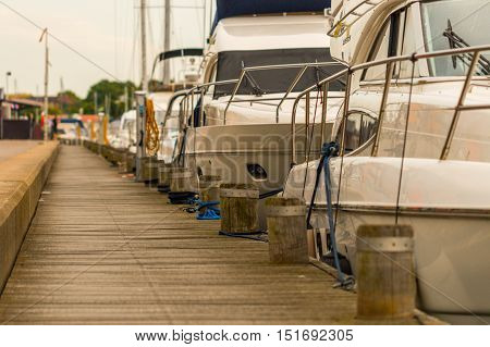 Several motorboat yachts are moored to the concrete jetty