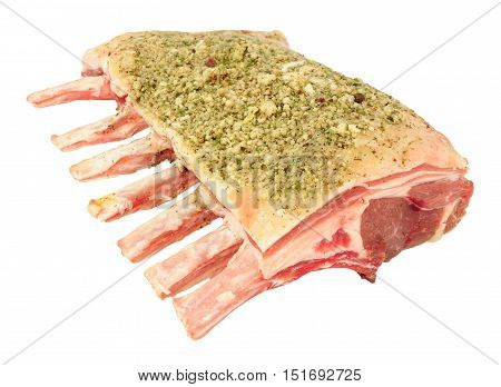 Rack of raw lamb cutlets with herb topping isolated on a white background