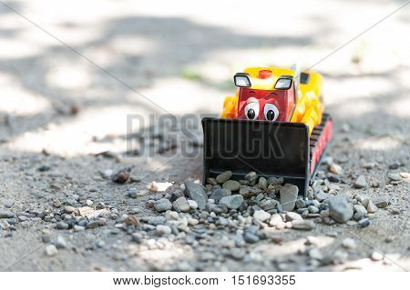 View of a colorful plastic bulldozer toy in the yard