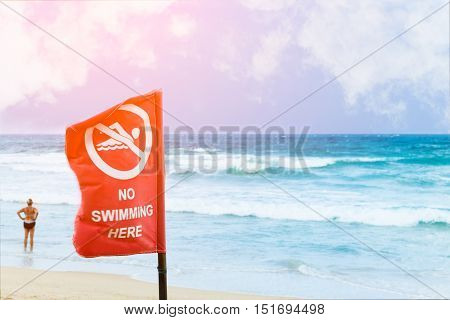 No swimming danger sign at the beach warning sign at the beach with people swim caution no swimming allowed.