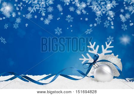 Blue ornament with white snow and snowflake on shiny blue background. Christmas background with silver and shiny balls with blue ribbon and copy space. Xmas holiday and blue decoration on white snow.