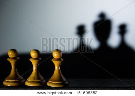 three chess pawn with one casting a king piece shadow in dark concept of strength and aspirations
