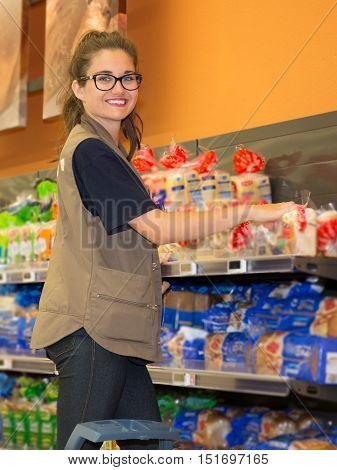 Merchandising. Sales assistant in supermarket arrange goods on supermarket shelves at store