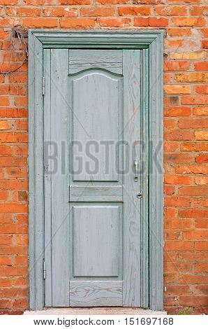 turquoise wooden doors in a brick wall