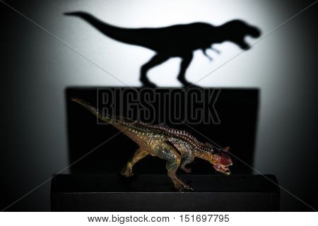 a carnotaurus casting a tyrannosaurus shadow in dark concept of strength and aspirations