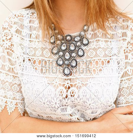 Beautiful jewelry at the girl in the chest. Vintage lace clothing