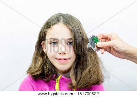 Lice treatment. Girl gets combed for lice with lice comb. Studio portrait.
