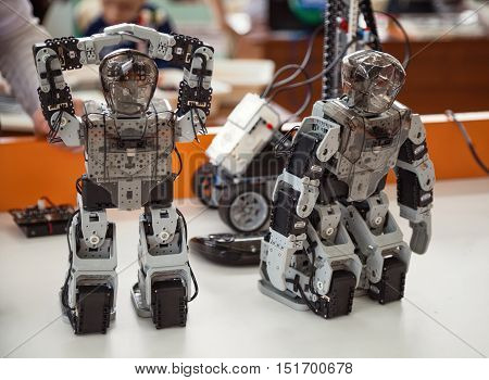 Khabarovsk Russia - April 24 2016: Robotis Bioloid Premium kit: 2 small programmed DIY humanoid robot toys standing on a table close-up