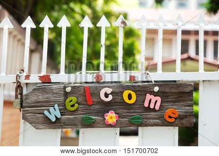 Fun colorful wooden welcome sign hanging on a white spiked fence