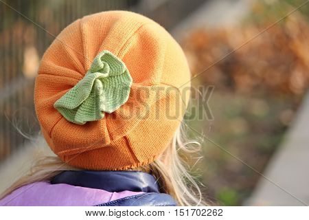 Knitted autumn orange hat in the form of a pumpkin. Clothes for Halloween.