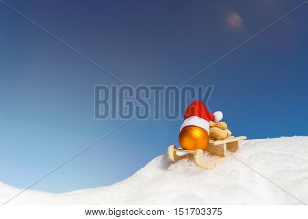 Wooden Sledge With A Christmas Ball, A Pointed Cap And Peanuts