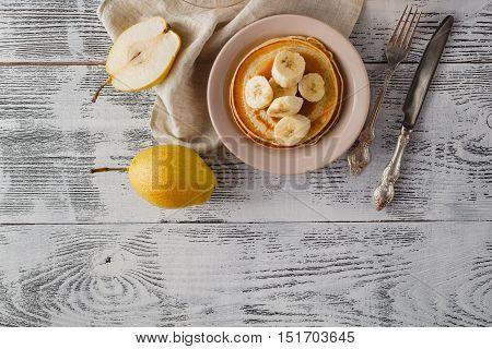 Pancakes With Banana & Walnut On Wood Background