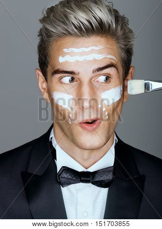 Funny classy man with cream lines on face spa treatment. Portrait of elegant man with perfect skin. Grooming himself