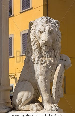 Closeup status of Marzocco heraldic lion with shield, symbol of Florence, in Piazza di Santa Croce in Florence, Italy.
