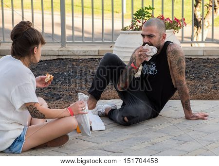 TEL-AVIV ISRAEL - OCTOBER 8 2016: Unidentified man and woman with tattoo eating outside