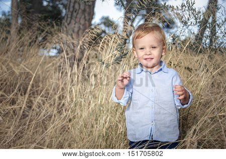 Portrait of a little boy near withered grass in autumn park.