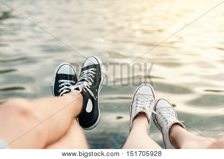 Young couple lying on the beach. Legs with sneakers near water