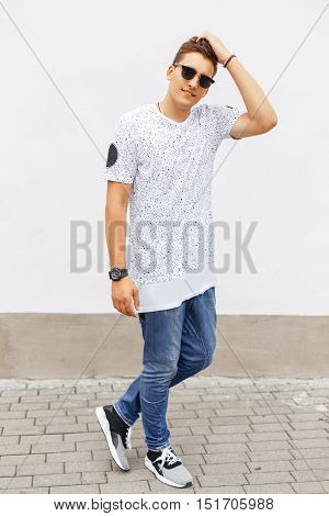 Young Handsome Man In A White T-shirt, Blue Jeans And Sneakers Standing Near A White Wall.