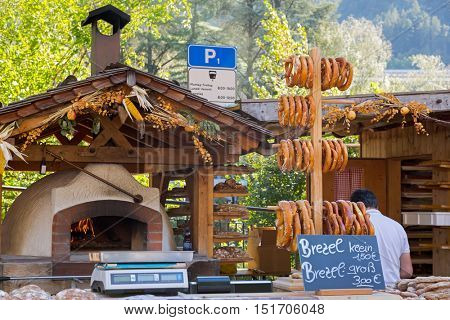 Small and big size of Pretzels selling in front of old traditional stone bread oven stove with burning wood fire and red flames inside