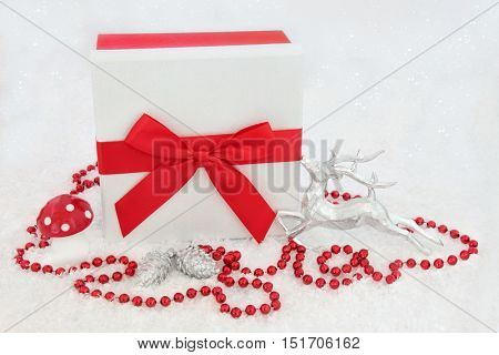 White glitter christmas present with red bow, silver reindeer, fly agaric mushroom, red beads and pine cone bauble decorations on snow background.