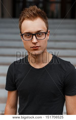Beautiful Stylish Young Guy In A Black Shirt And Hipster Glasses.