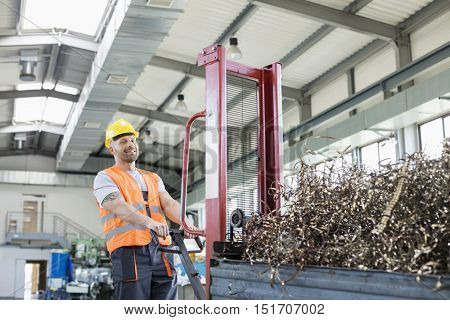 Portrait of mid adult worker pulling hand truck loaded with steel shavings in factory