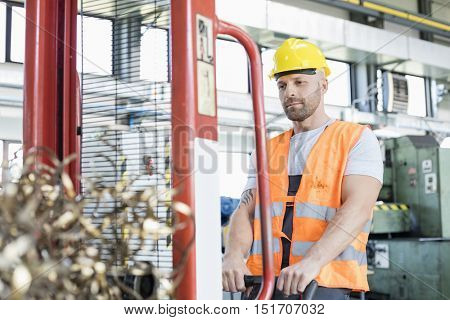 Mid adult worker pulling hand truck with steel shavings in factory