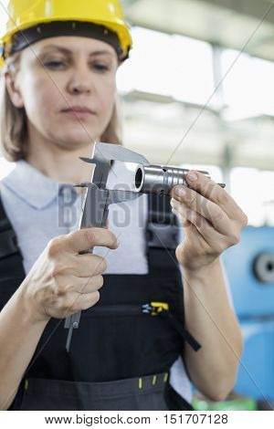 Mature female worker measuring metal with caliper in factory