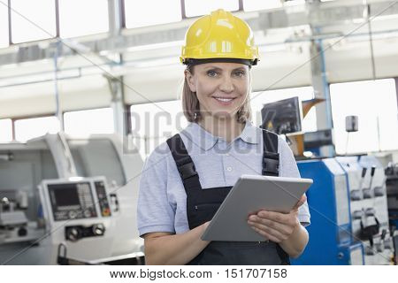 Portrait of smiling female worker using digital tablet in manufacturing industry