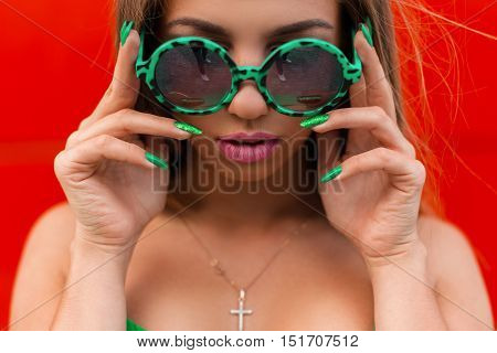 Close-up Bright Portrait Of A Beautiful Stylish Woman In Green Round Sunglasses On A Red Background.