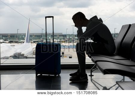 A teenager is waiting on an airport for departure