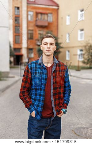Handsome Man In A Checkered Shirt On The Background Of Buildings