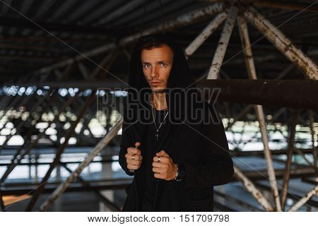 Handsome Man In A Black Hood Near Metal Pipes