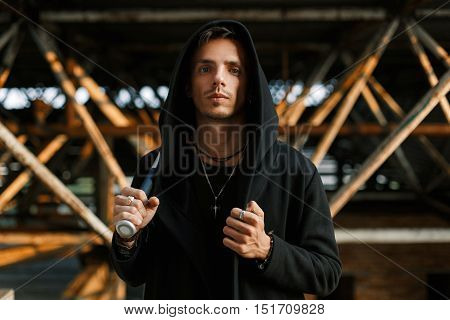 Stylish Handsome Man In A Black Robe With A Hood Holds A Bat.