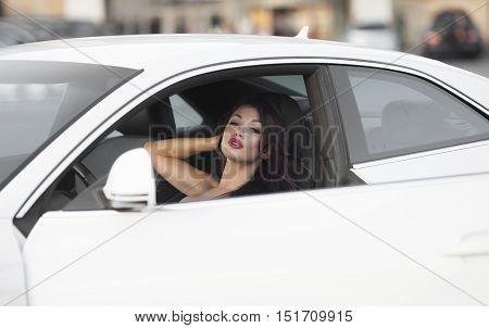 Portrait of beautiful sexy fashion woman model with bright makeup sitting in a car