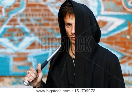 Stylish Handsome Man In Black Clothes With A Hood Standing Near A Brick Wall With Graffiti. Man Hold