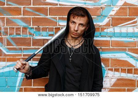 Angry Guy Near Brick Wall With Graffiti Holding A Metal Bat