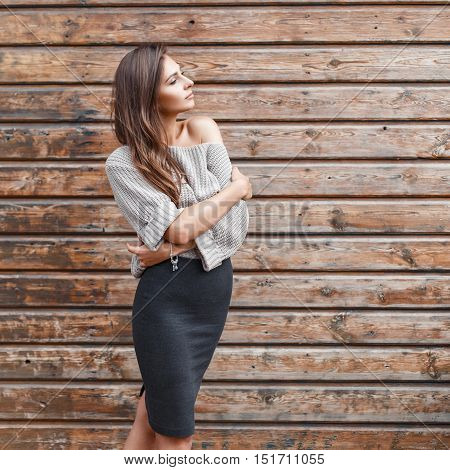 Beautiful Young Woman With Hair In A Sweater Posing Near The Wooden Wall